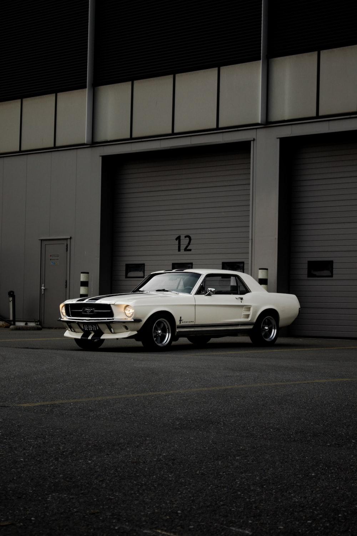 white chevrolet camaro parked in front of garage