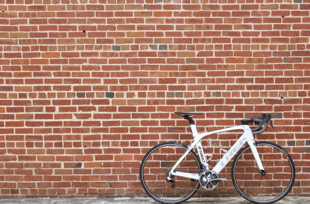 white and black road bike leaning on brown brick wall