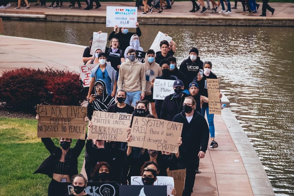people holding signage standing on sidewalk during daytime