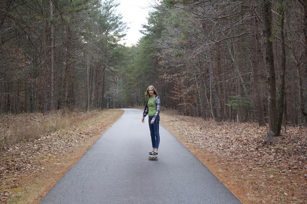 woman in blue jacket standing on gray asphalt road between trees during daytime