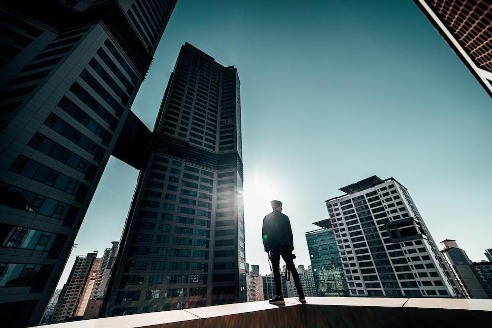 man in black jacket and pants walking on sidewalk near high rise buildings during daytime