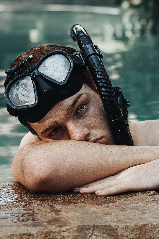 man wearing black goggles on swimming pool during daytime