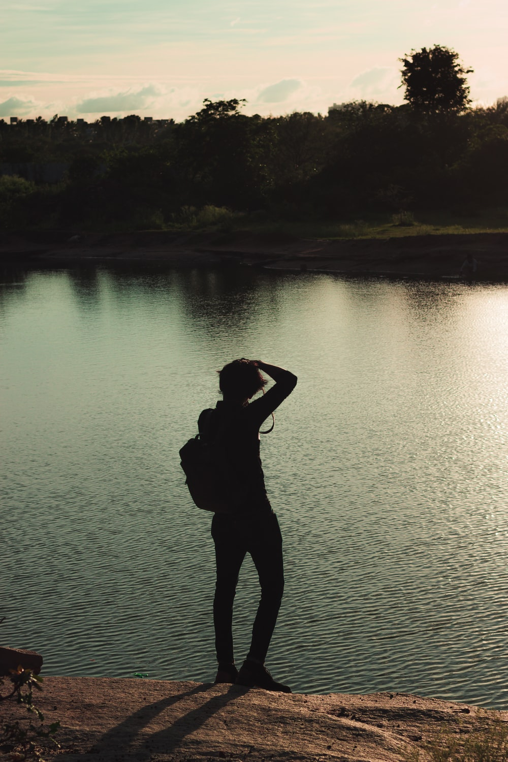 silhouette of woman standing on lake shore during daytime