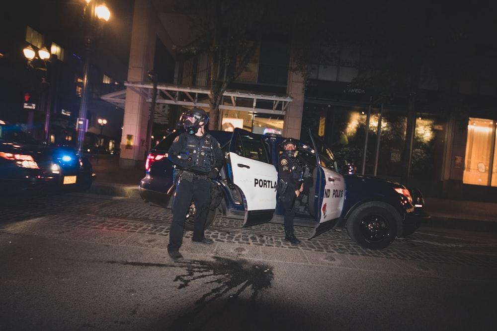 man in black jacket and black pants walking on sidewalk during night time
