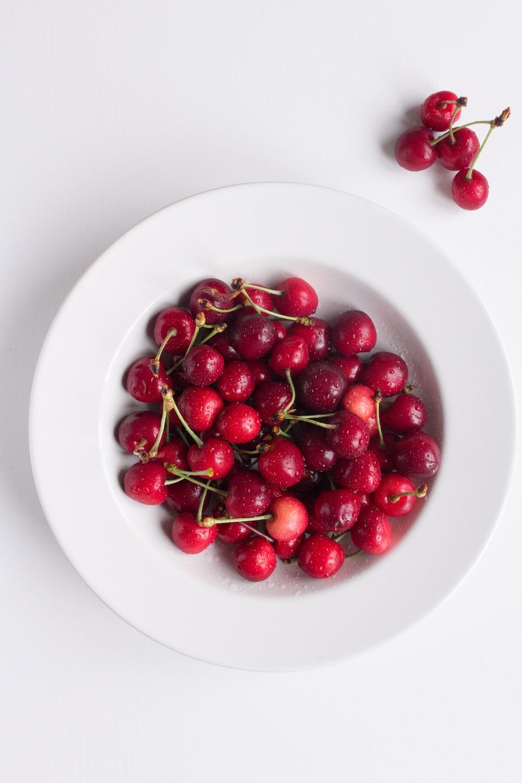 red cherries on white ceramic plate
