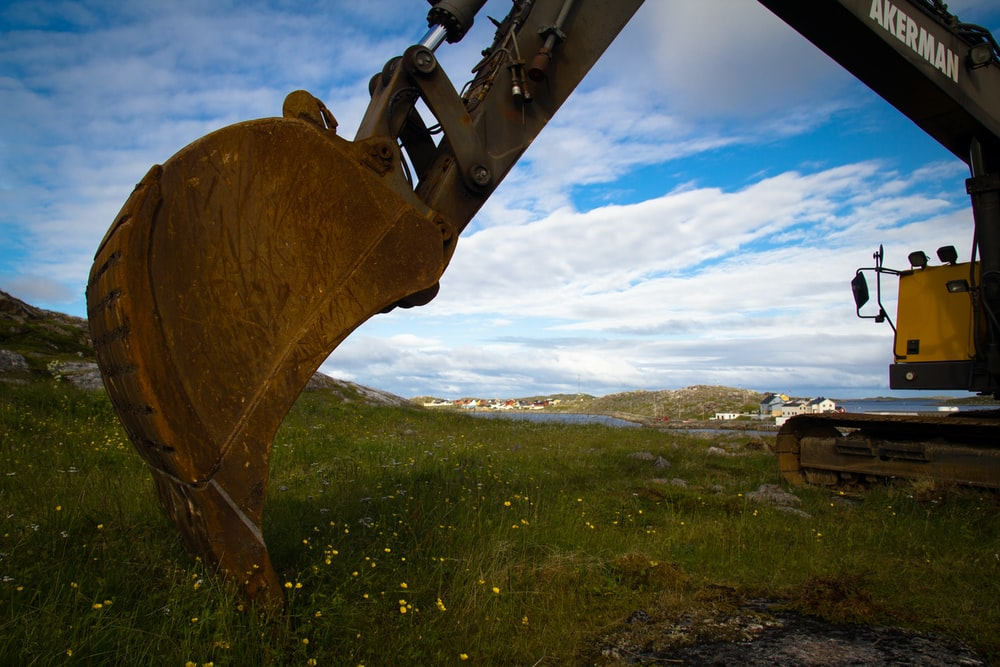 brown metal machine on green grass field under blue sky and white clouds during daytime