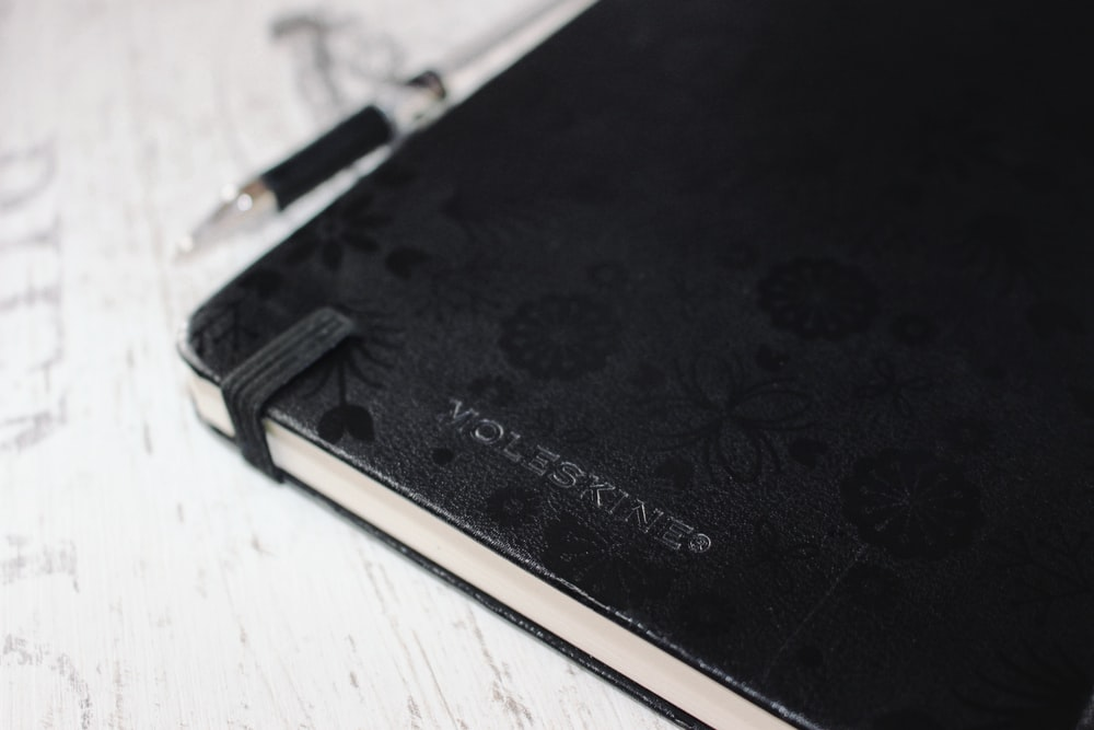black leather case on white wooden table