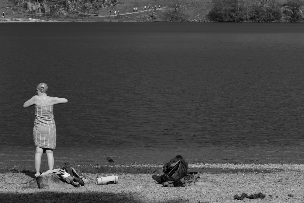 grayscale photo of person sitting on rock near body of water
