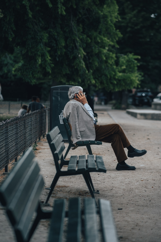 man in brown jacket sitting on bench