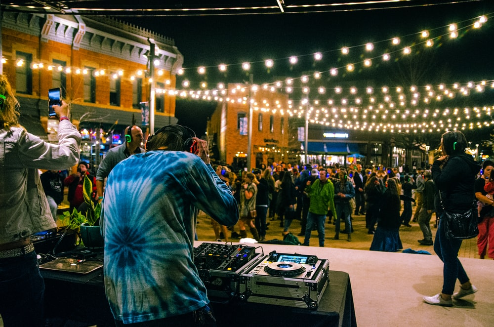 man in blue and white long sleeve shirt standing in front of people during nighttime