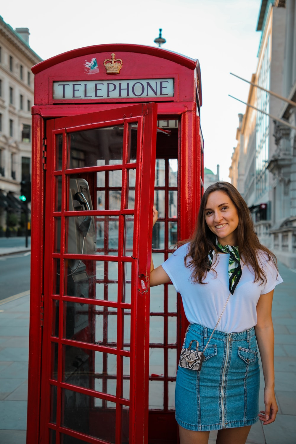 woman in white shirt and blue denim shorts standing beside red telephone booth during daytime