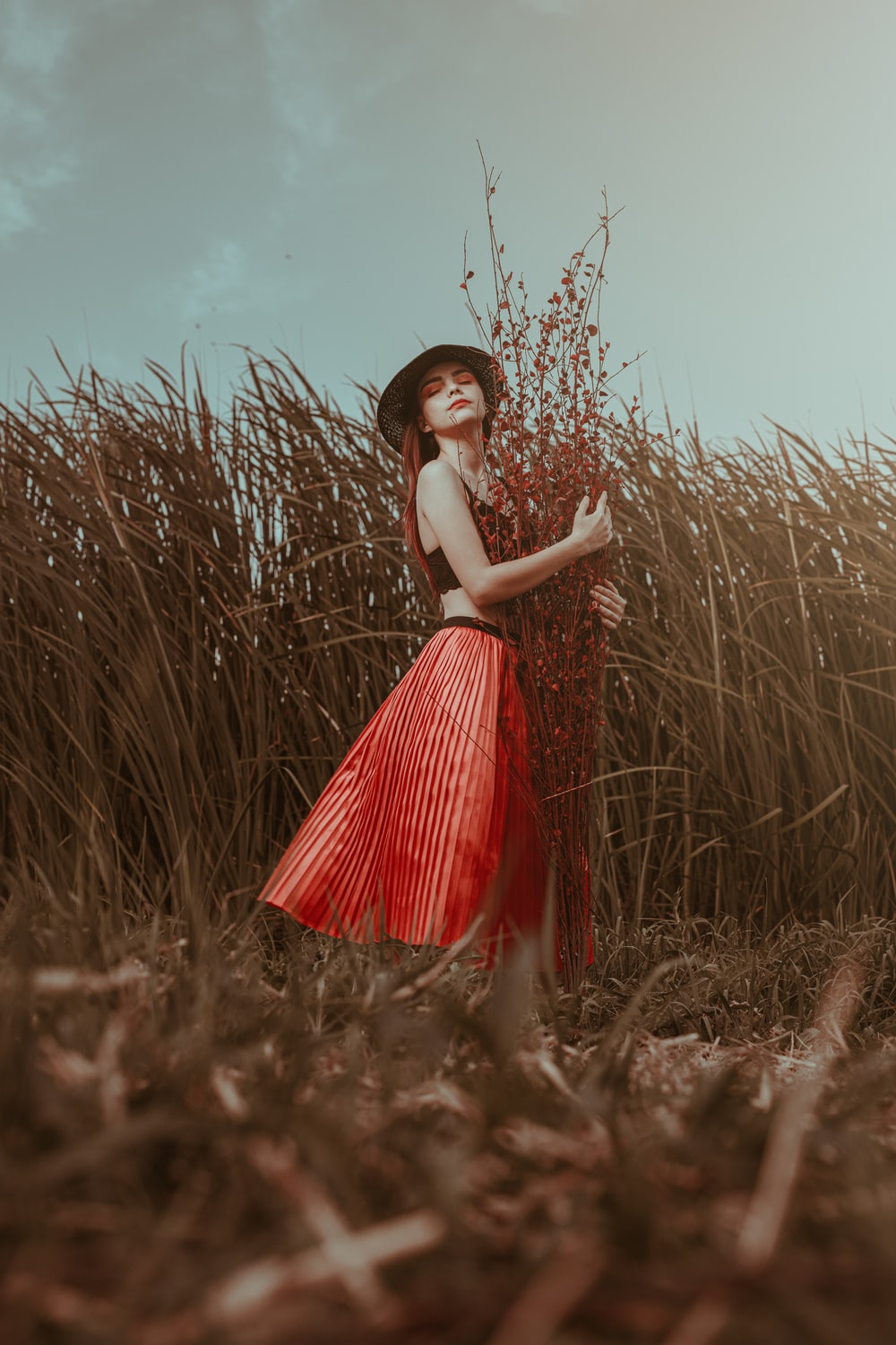 woman in red and white dress standing on brown grass field during daytime