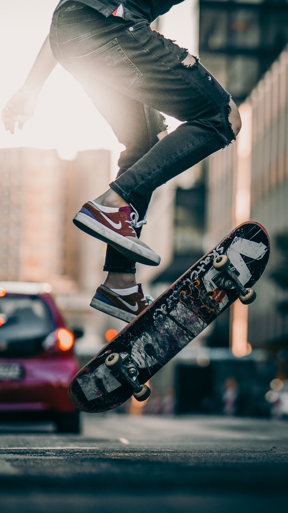 person in black pants and black and white sneakers jumping on skateboard