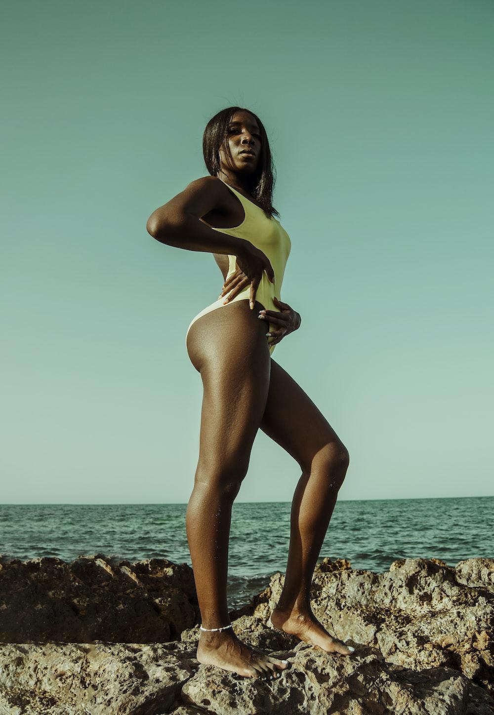 woman in yellow bikini standing on rocky shore during daytime