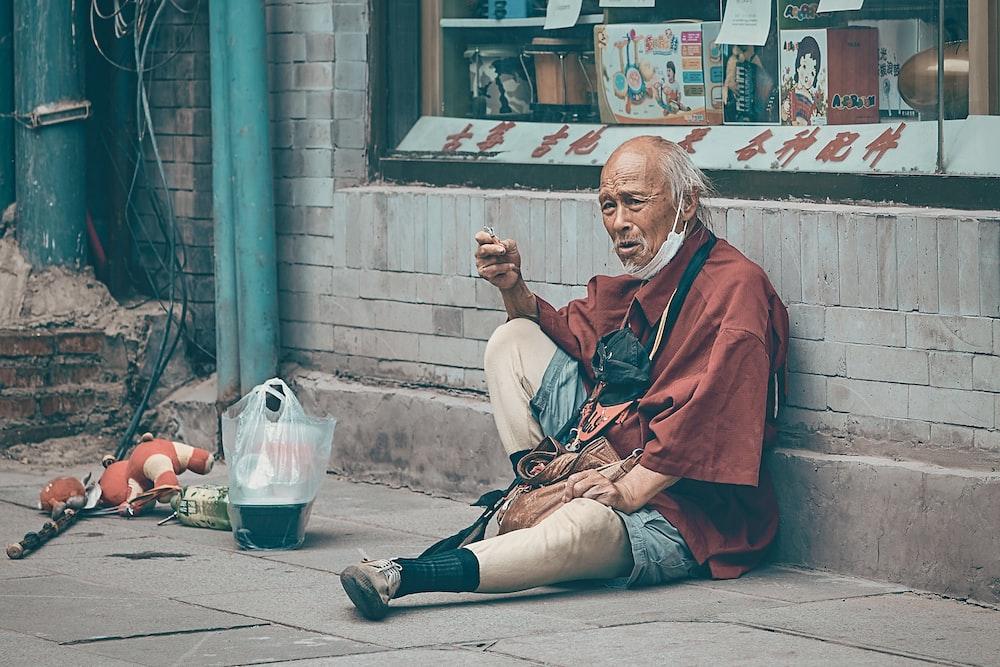 man in red robe sitting on floor