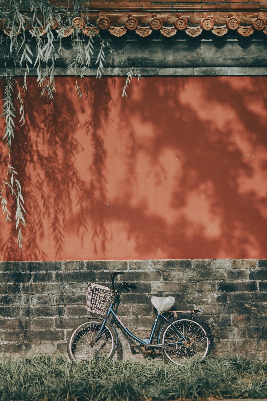 black city bike beside brown wall