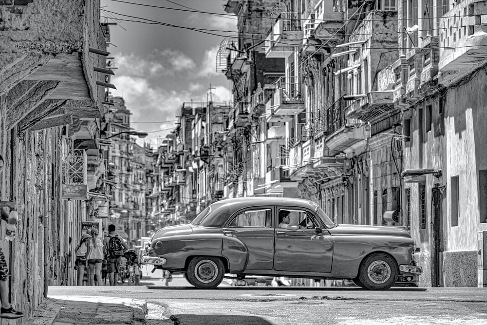 grayscale photo of classic car on street