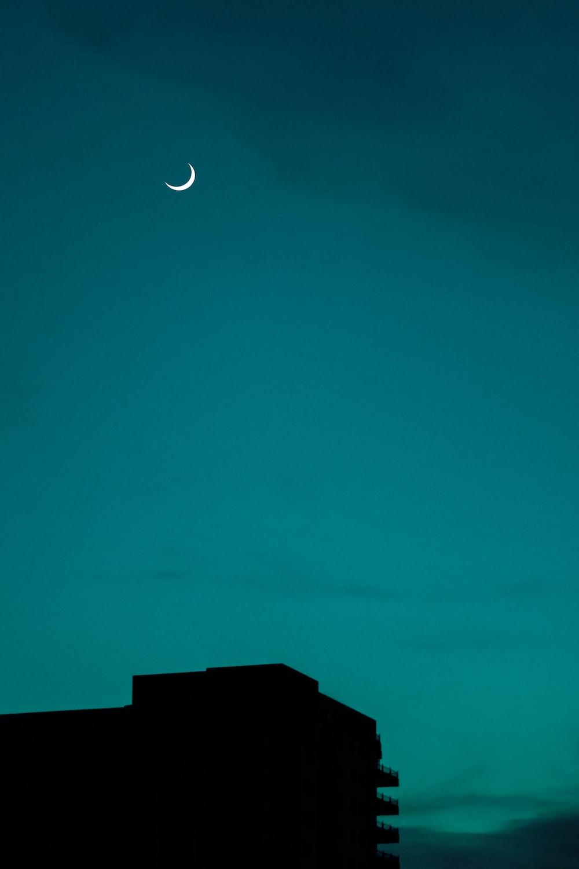 crescent moon over black building