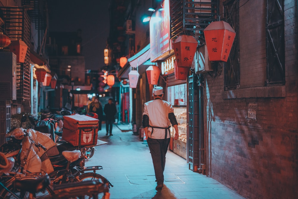 woman in pink coat walking on sidewalk during night time