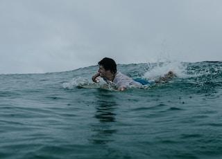 man in blue swimming trunks in water