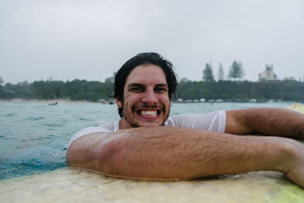 man in white tank top smiling
