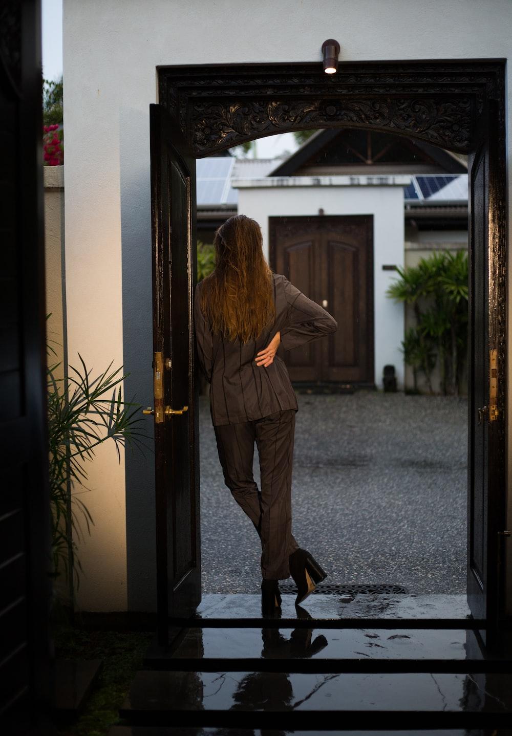 woman in brown coat standing near door