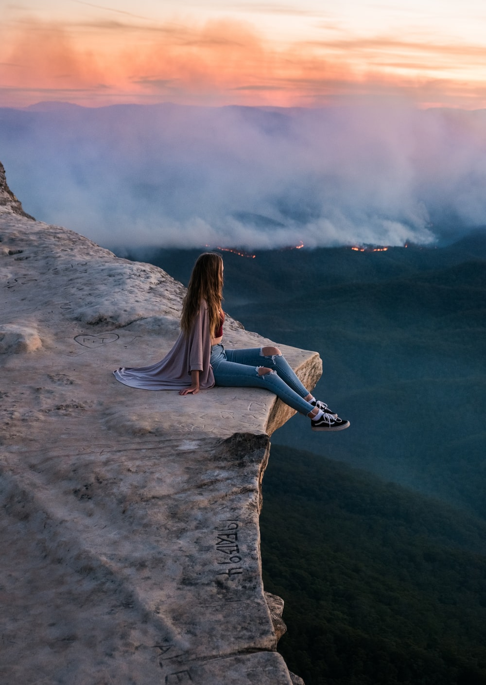 woman in blue denim jeans sitting on rock formation during daytime