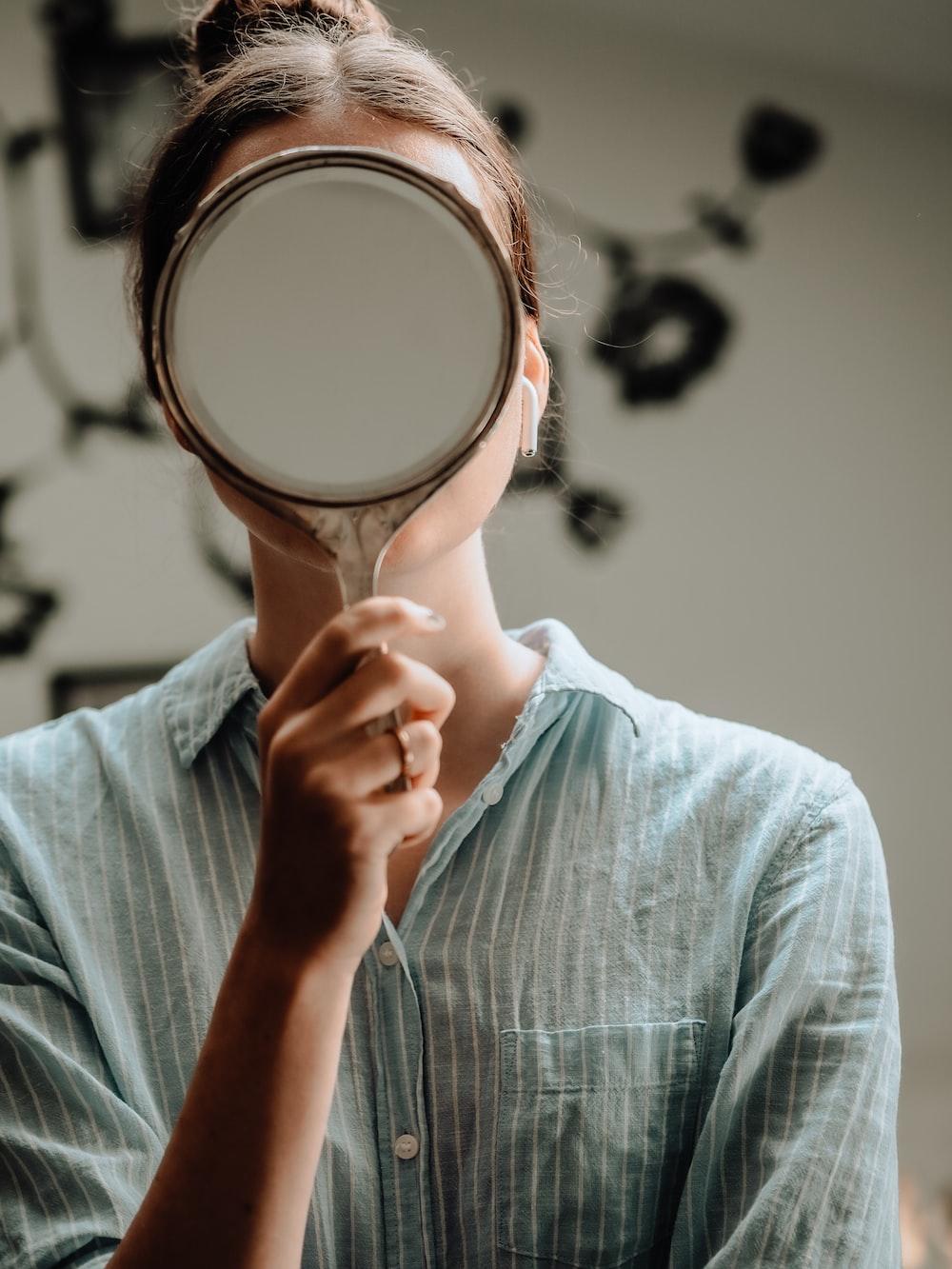 person in blue crew neck shirt holding brown round mirror