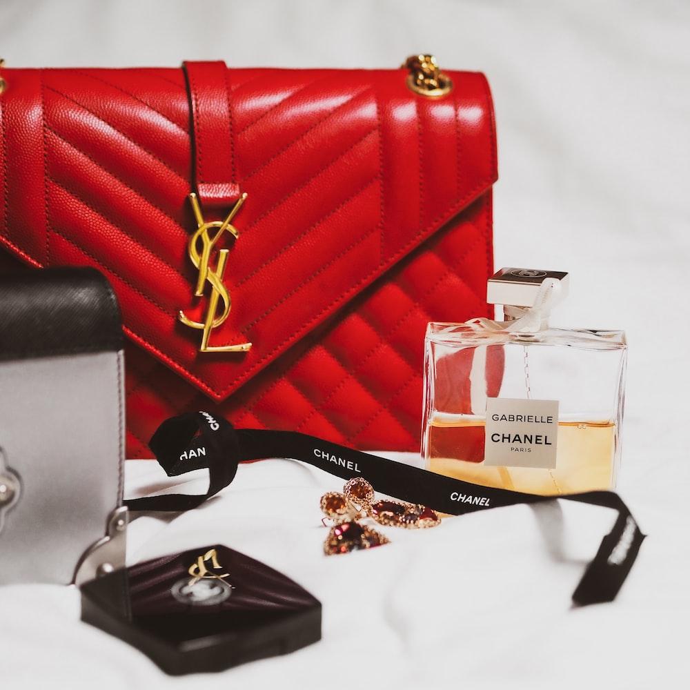 black framed eyeglasses beside red leather handbag