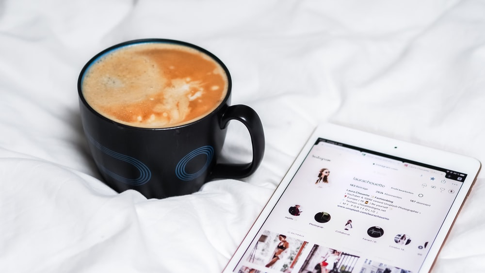 black ceramic mug with brown liquid inside