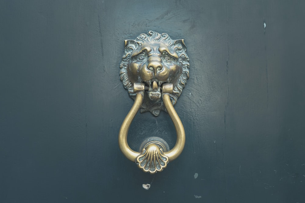 gold lion door handle on blue wooden door