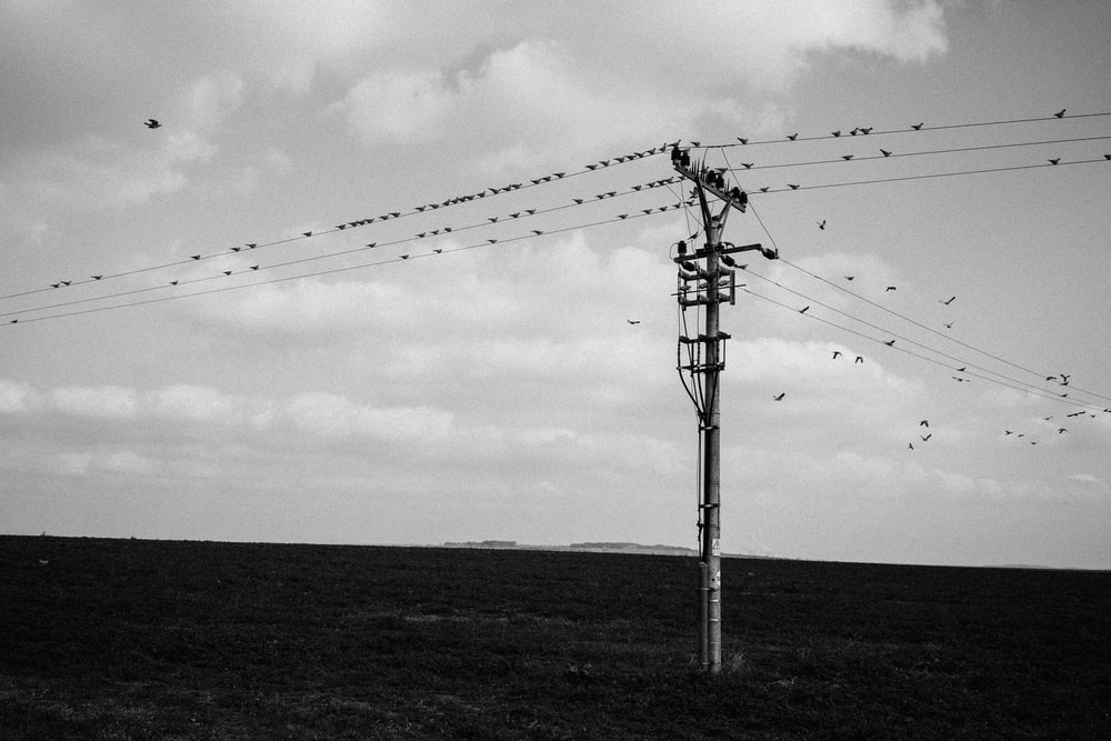 grayscale photo of electric post under cloudy sky