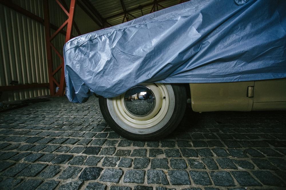 blue car cover on gray brick floor