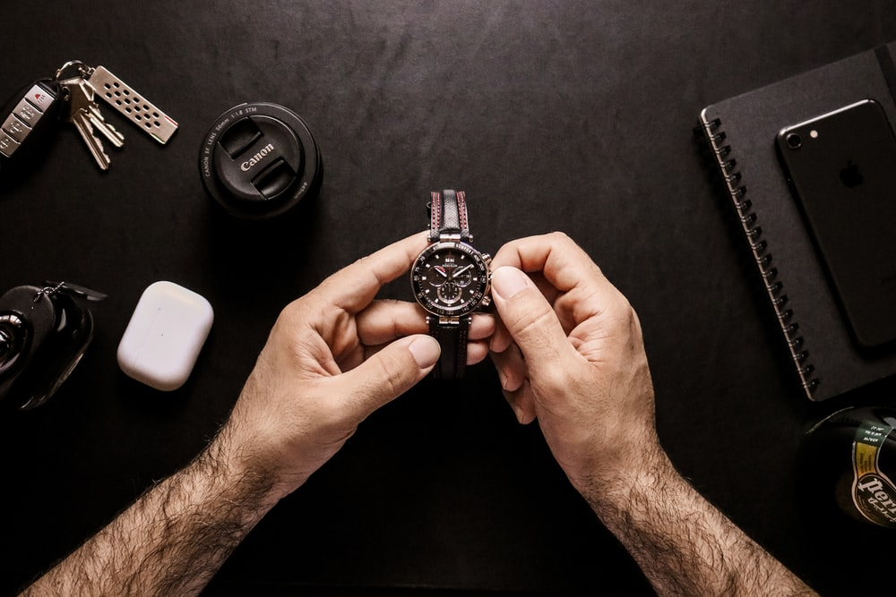 person holding silver and black round analog watch