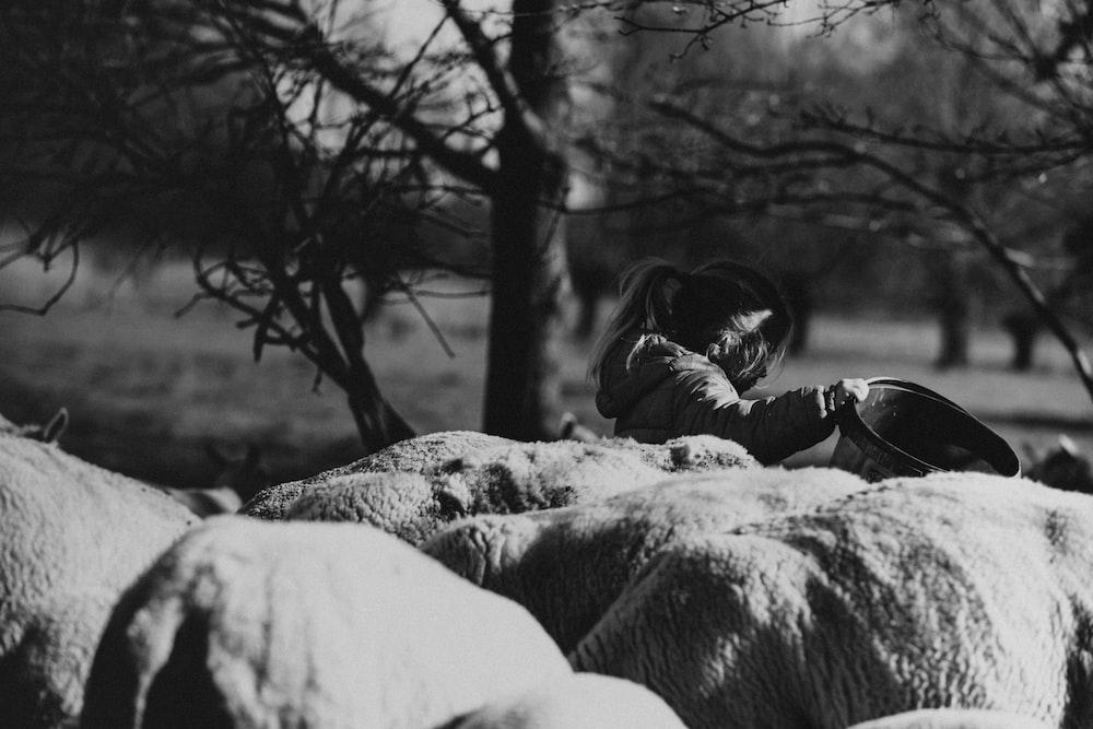 grayscale photo of woman lying on rock