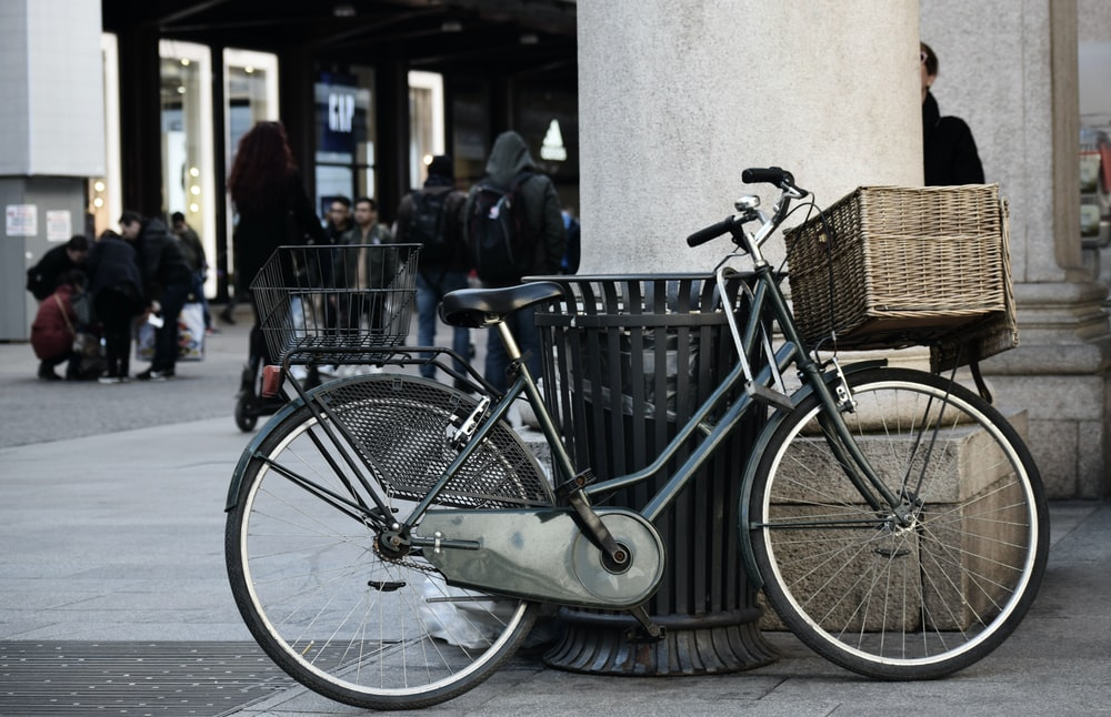 blue city bike parked beside brown wooden bench