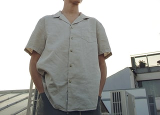 man in white button up shirt standing during daytime