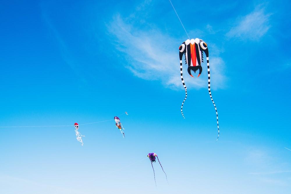 orange and black kite flying under blue sky during daytime