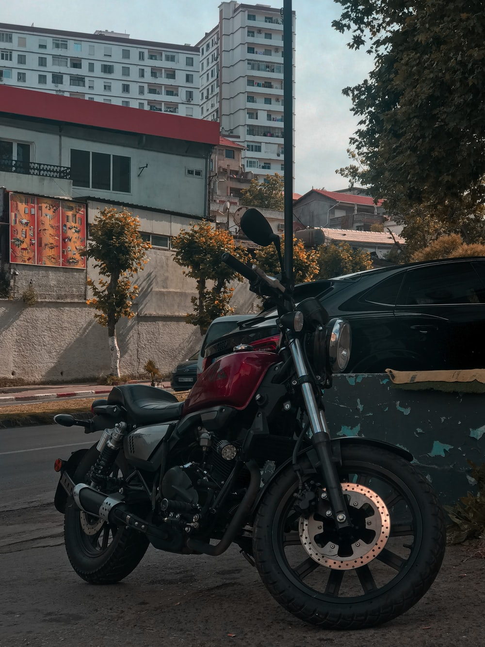 black and red motorcycle parked beside black suv during daytime