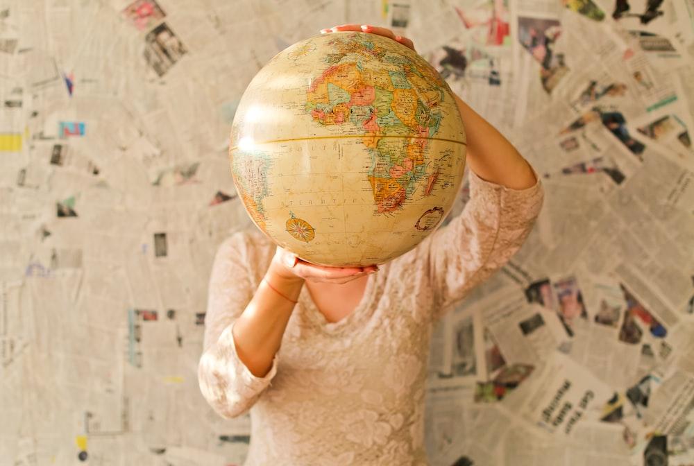 woman in white lace dress holding desk globe