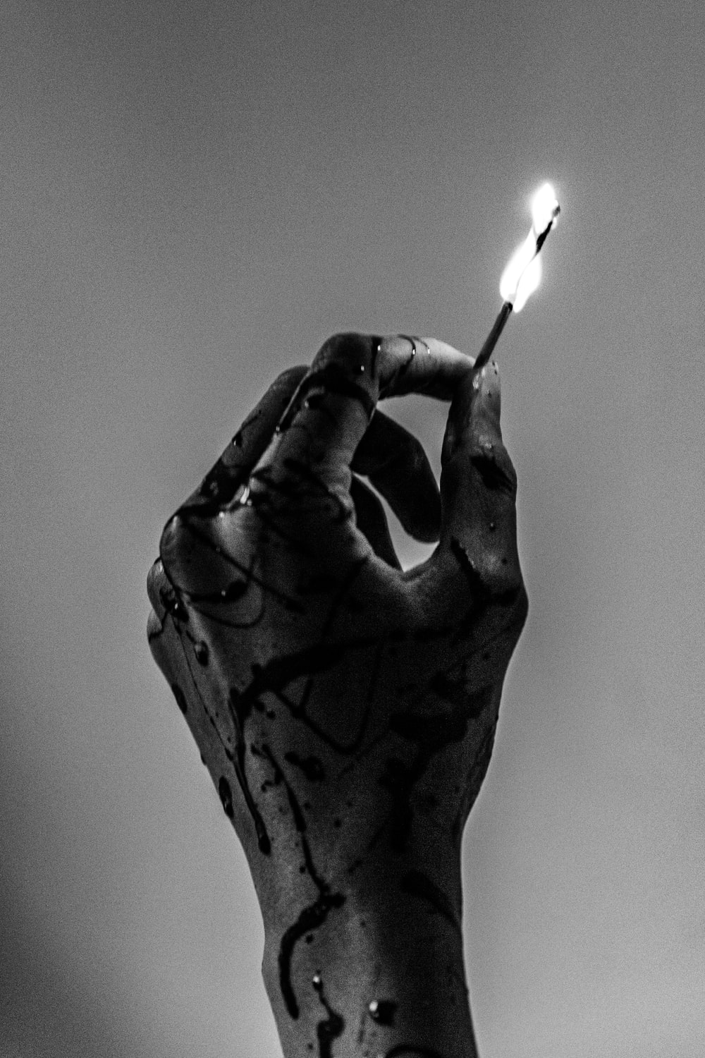 grayscale photo of person holding lighted match stick