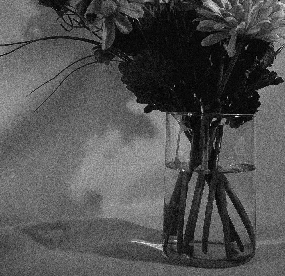 grayscale photo of flowers in clear glass vase