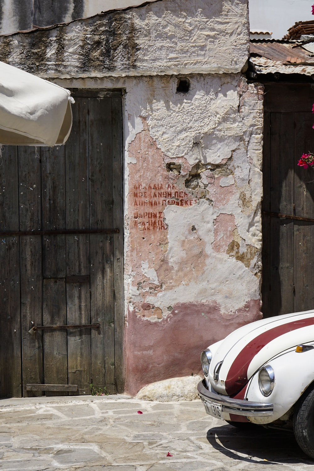 red and white car parked beside brown wooden door