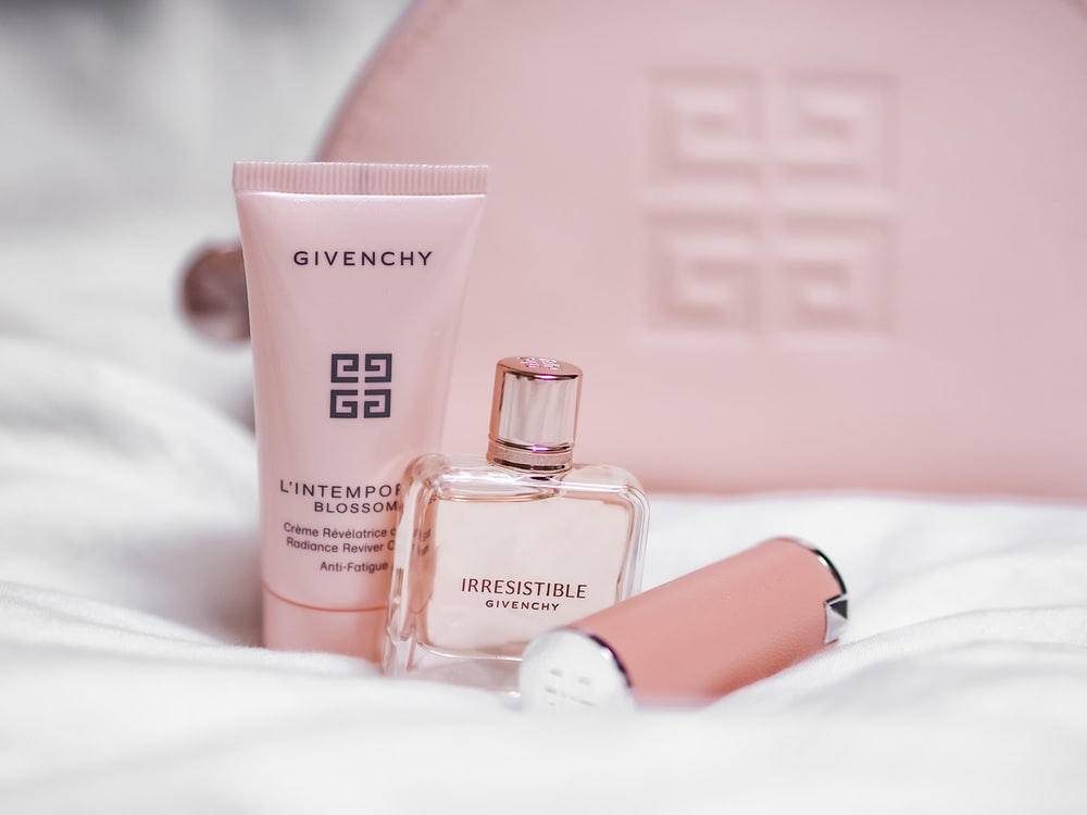 two perfume bottles on white textile