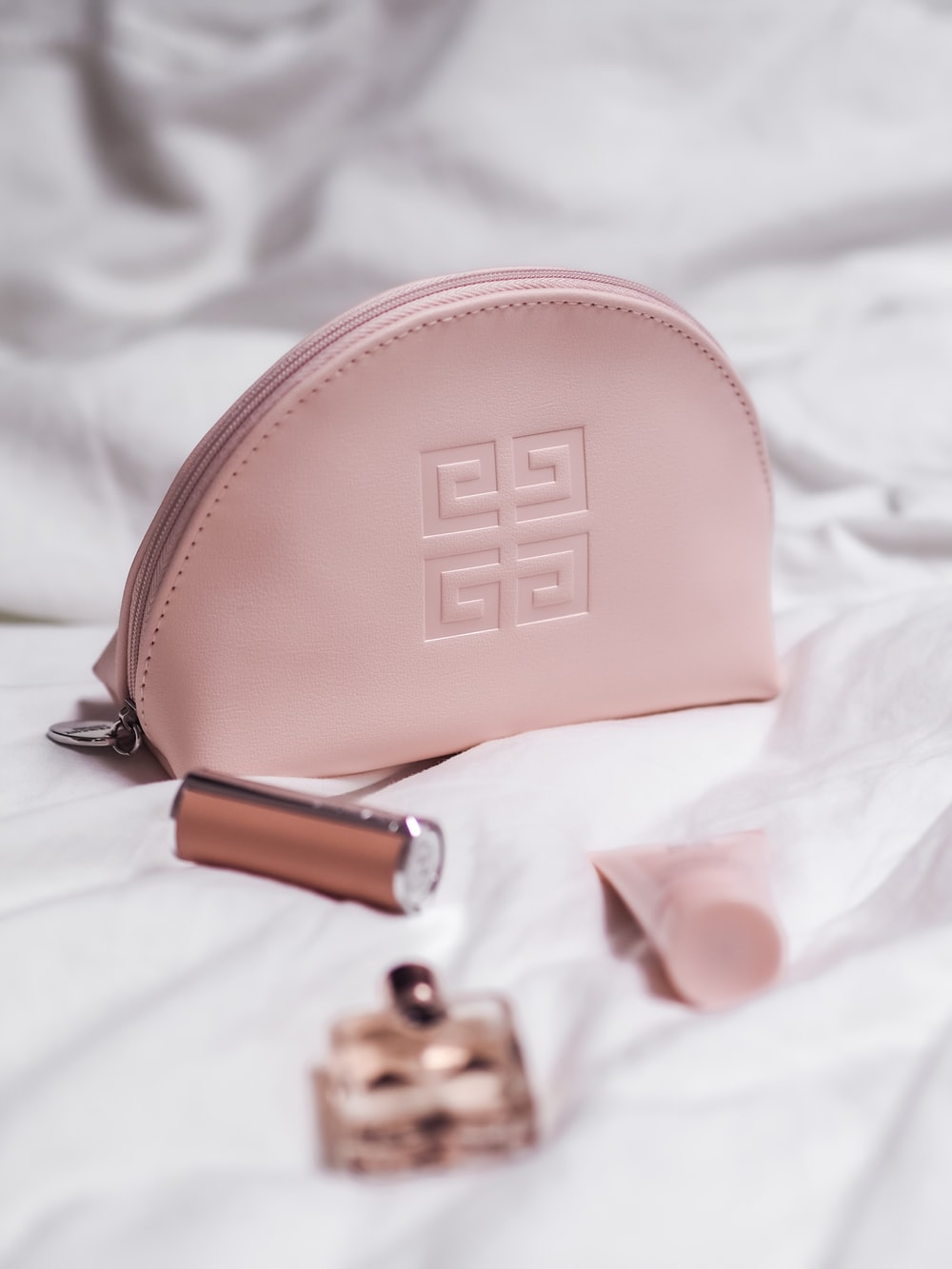 pink leather sling bag on white textile
