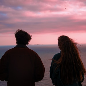 couple standing on seashore during sunset