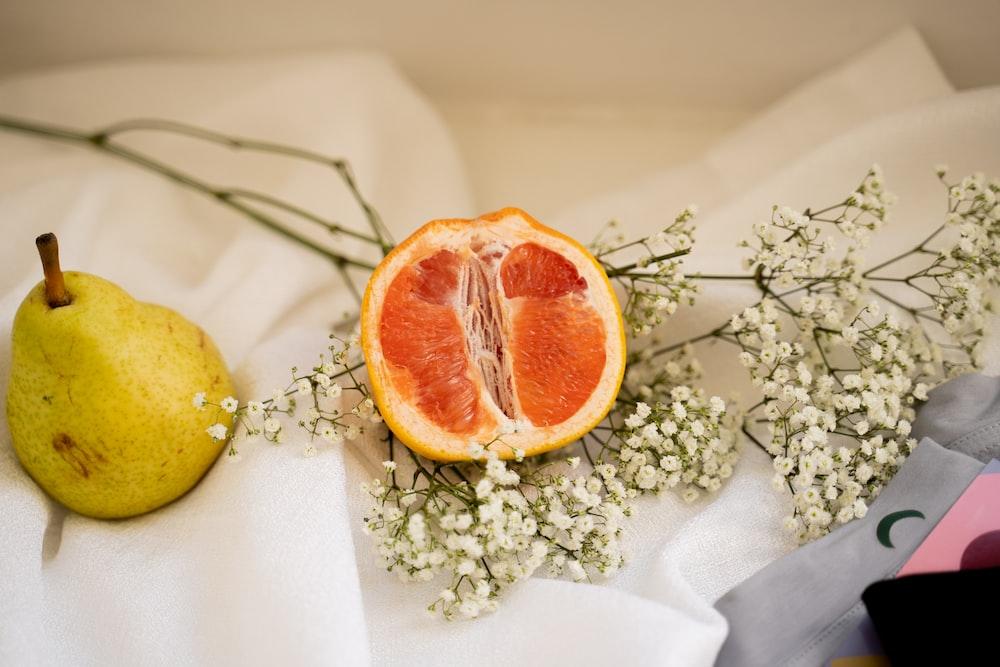 sliced orange fruit on white textile