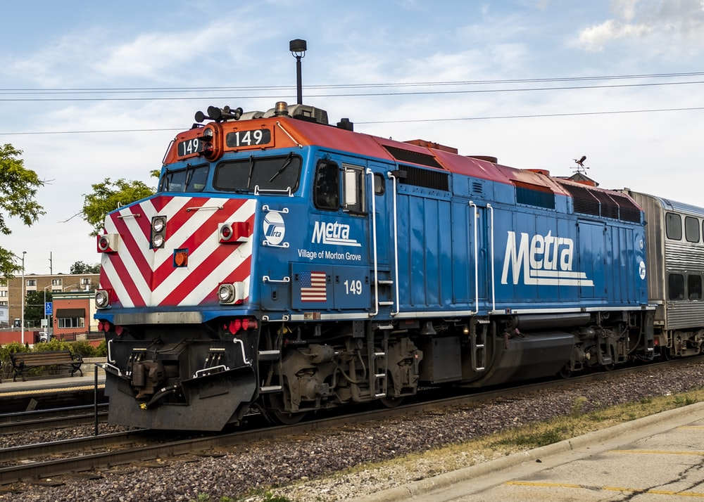 blue red and white train on rail track during daytime