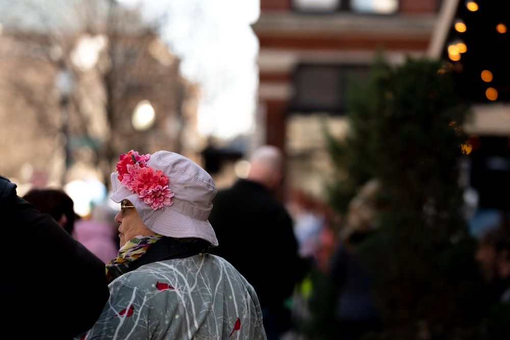 person in gray and red floral shirt with white and pink flower on head