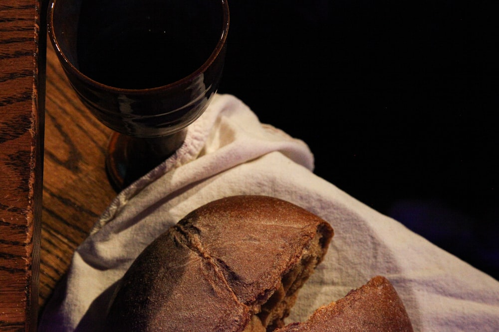bread on white textile beside clear drinking glass